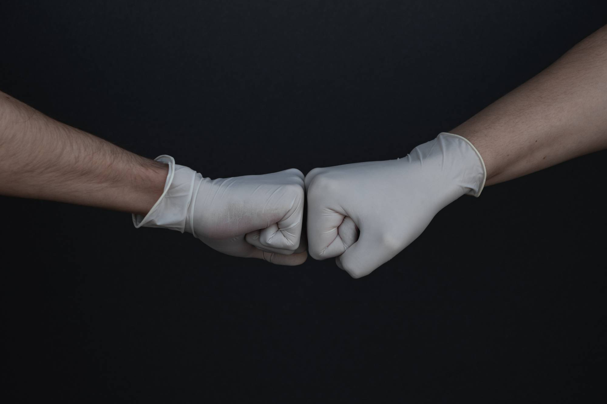 Two hands in gloves doing a fist bump